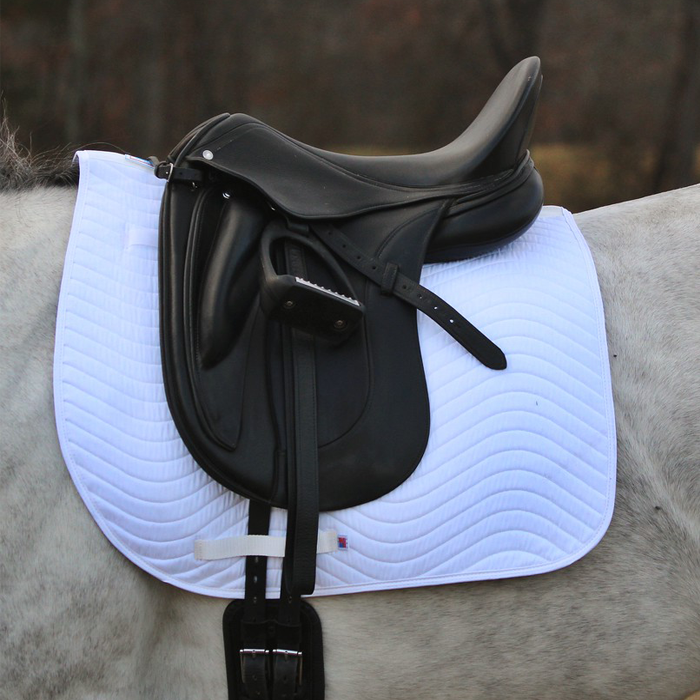 white dressage saddle pad with saddle
