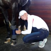 Grand Prix Dressage rider Katherine Bateson Chandler wrapping a horse's leg with Draper Recovery Wraps.